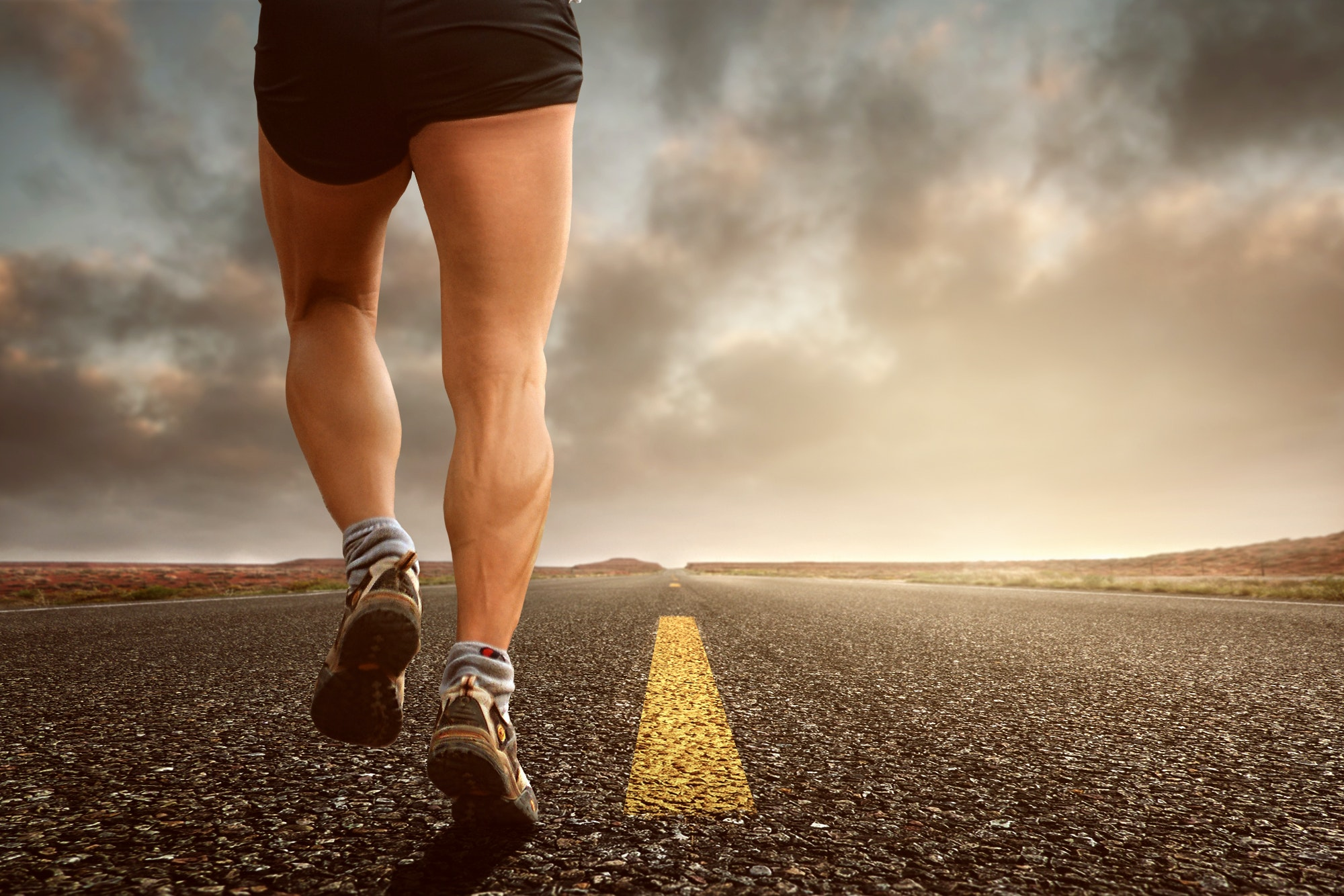 Photo of a man running showing just his lower half and legs in the middle of the road